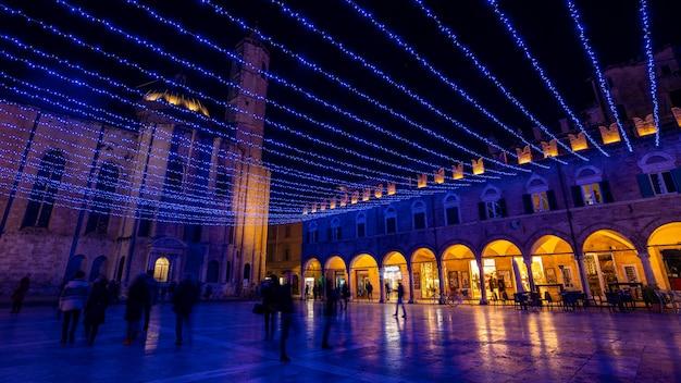 Ludzie chodzą na placu ludowym w nocy z świątecznych dekoracji