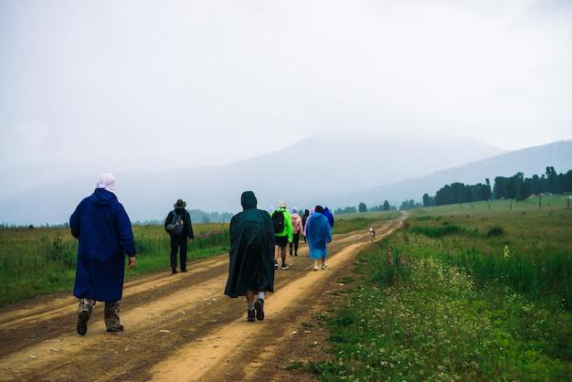 Ludzie chodzą naprzód w górach pomimo złej pogody.