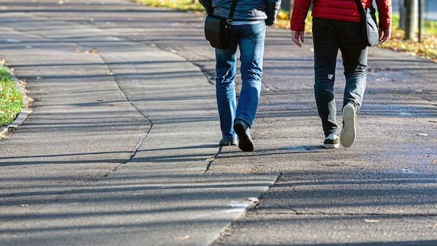 Ludzie chodzą po chodniku asfaltowym w słoneczny dzień, nogi z bliska cień