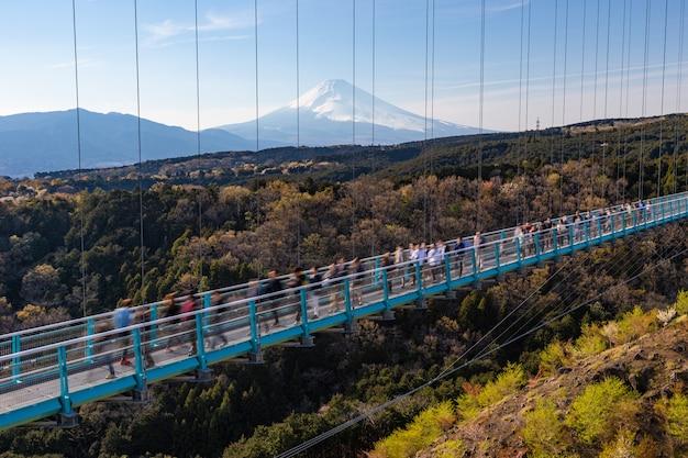 Ludzie chodzą po moście mishima skywalk z mount fuji widzianym w oddali