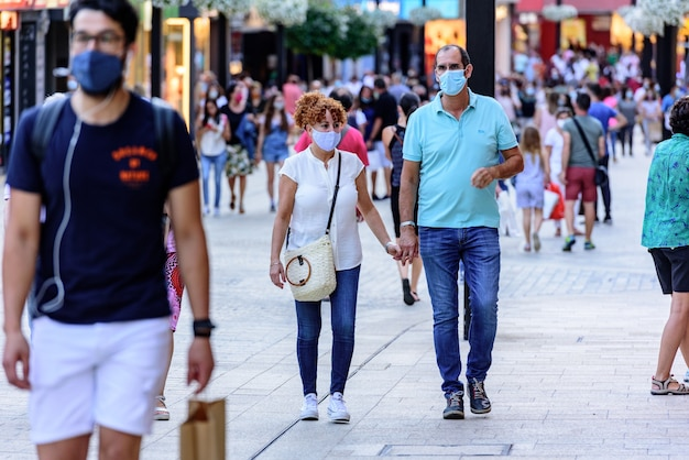 Ludzie chodzą po ulicy handlowej o nazwie meritxell na cześć covid19