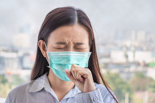 Ludzie chorują z powodu zanieczyszczenia powietrza, środowisko ma szkodliwe lub trujące skutki. kobieta w mieście nosząca maskę na twarz, aby się chronić, ponieważ poziom zanieczyszczenia powietrza rośnie.