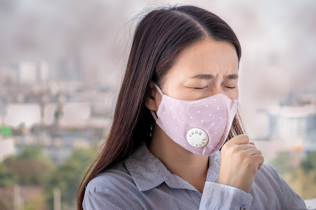 Ludzie chorują z powodu zanieczyszczenia powietrza, środowisko ma szkodliwe lub trujące skutki. kobieta w mieście w masce na twarz, aby się chronić