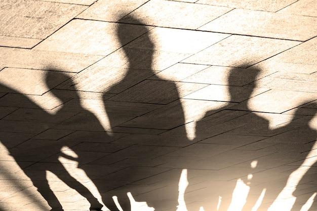 Ludzie, cienie i sylwetki ludzi na chodniku, chodniku w świetle poranka