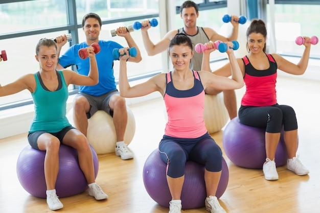 Ludzie ćwiczy z dumbbells na sprawności fizycznych piłkach