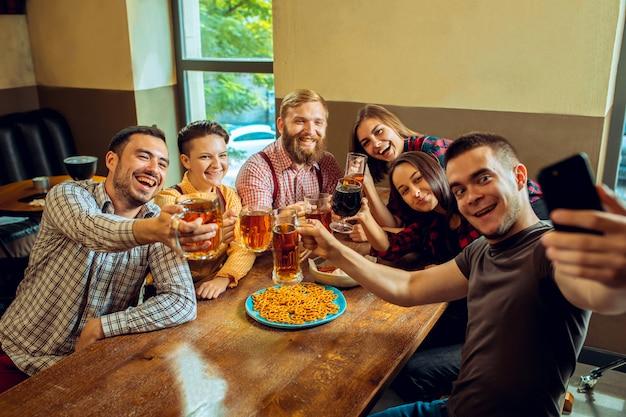 Ludzie, czas wolny, przyjaźń i komunikacyjny pojęcie, - szczęśliwi przyjaciele pije piwo, opowiada i brzęka szkła przy barem lub pubem
