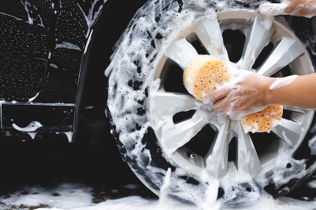 Ludzie człowiek trzymając rękę żółta gąbka do mycia samochodu. czyszczenie opony koła. myjnia samochodowa koncepcyjna czysta.