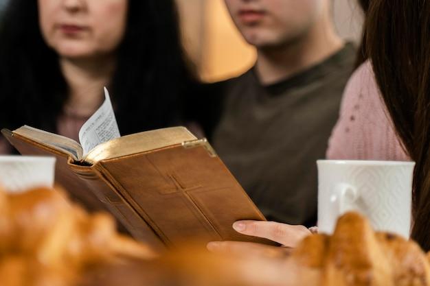 Ludzie czytający biblię podczas kolacji