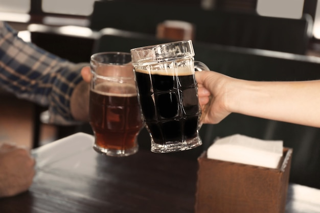 Ludzie dopingujący szklanki do piwa nad stołem w pubie, zbliżenie