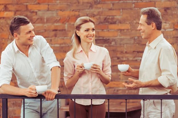 Ludzie dyskutują o sprawach biznesowych, piją kawę.