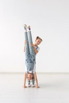 Ludzie, dzieci i koncepcja akrobatyczna - małe bliźniaczki robi ćwiczenia na białym tle.