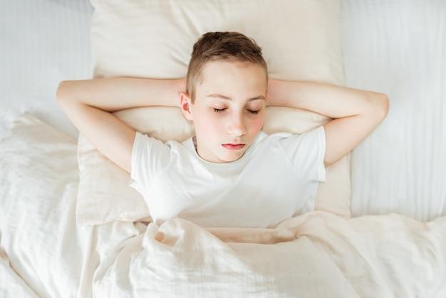 Ludzie dzieci, koncepcja odpoczynku i komfortu - teen chłopiec śpi w łóżku w domu