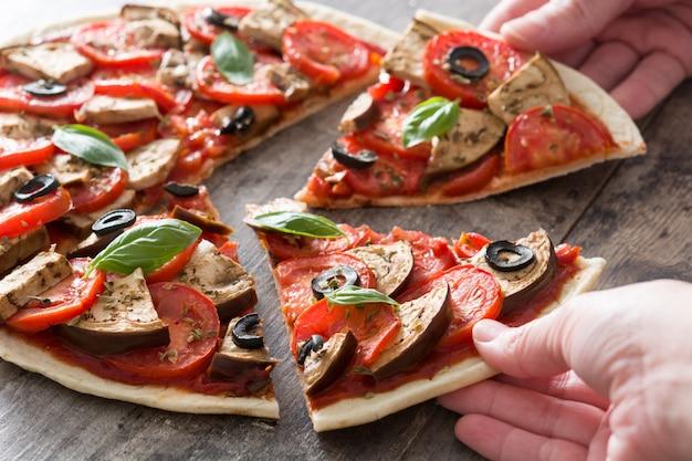 Ludzie dzielący wegetariańską pizzę z bakłażanem, pomidorem, czarnymi oliwkami, oregano i bazylią na drewnianej powierzchni
