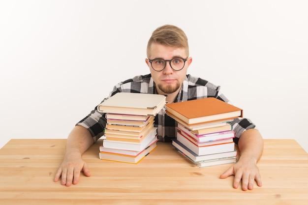 Ludzie, egzamin i koncepcja edukacji - wyczerpany i zmęczony student ubrany w kraciastą koszulę siedzi przy drewnianym stole z wieloma książkami