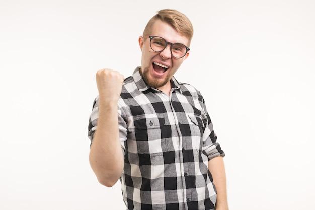 Ludzie, emocje i koncepcja triumfu - podekscytowany i szczęśliwy młody człowiek ubrany w koszulę pokazując pięść