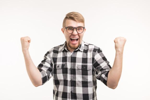 Ludzie, emocje i koncepcja triumfu - podekscytowany i szczęśliwy młody człowiek ubrany w koszulę pokazując pięści na białej powierzchni.