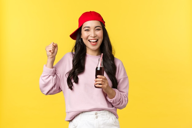 Ludzie emocje, napoje i koncepcja letniego wypoczynku. entuzjastyczna szczęśliwa azjatycka dziewczyna delektująca się napojem gazowanym, pijąca napój i tańcząca, uśmiechnięta wesoło, stojąca na żółtym tle