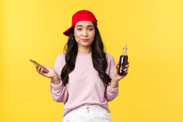 Ludzie emocje, napoje i koncepcja letniego wypoczynku. niezdecydowana, niezdecydowana, słodka azjatka w czerwonej czapce, trzymająca butelkę z napojem i telefonem komórkowym, wzruszając niepewnie, żółtym tłem.