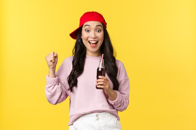 Ludzie emocje, napoje i koncepcja letniego wypoczynku. zaskoczony, podekscytowany ładna azjatycka dziewczyna w czerwonej czapce, pijący napój gazowany i śpiewający, oglądający grę sportową, cieszący się wakacjami, żółte tło.