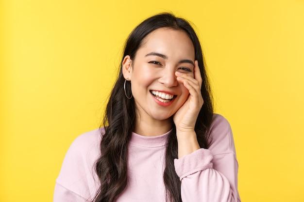 Ludzie emocje, styl życia koncepcja wypoczynku i piękna. piękna azjatycka dziewczyna dotyka twarzy i śmieje się ze szczęśliwym wesołym uśmiechem, słyszy komplement i rumieniąc się, stoi na żółtym tle.