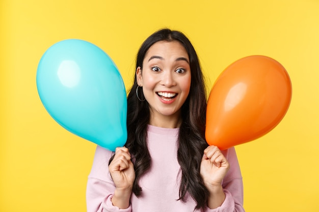 Ludzie emocje, styl życia koncepcja wypoczynku i piękna. wesoła szczęśliwa azjatka gratuluje wielkiego święta, trzymając dwa balony i szeroko uśmiechając się, ciesz się imprezą na żółtym tle.