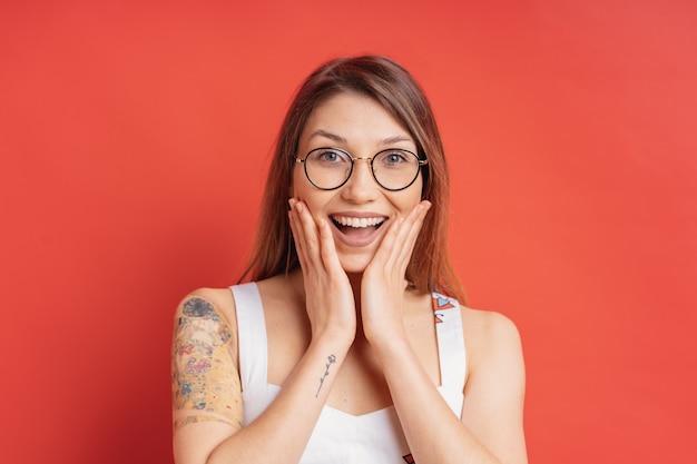 Ludzie emocji - portret zaskoczony pozytywnej dziewczyny na czerwonej ścianie