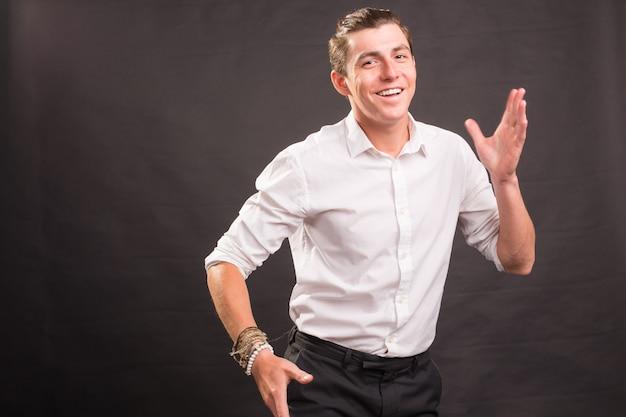 Ludzie Gest I Koncepcja Mody Młody Przystojny Mężczyzna Macha Ręką Na Brązowej Powierzchni Premium Zdjęcia