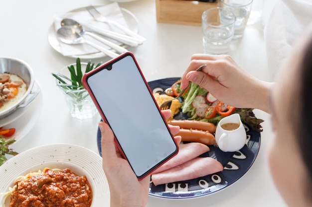Ludzie grający na smartfonie podczas jedzenia śniadania. białe miejsce na dodanie tekstu.