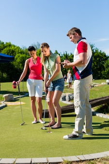 Ludzie grający w mini golfa na świeżym powietrzu