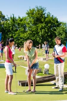 Ludzie grający w miniaturowe golfa na zewnątrz