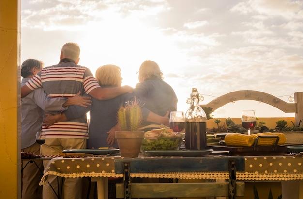 Ludzie grupa starszych przyjaciół przytula się i celabruje razem, oglądając zachód słońca golde z tarasu na dachu, żyjąc zawsze na wakacjach i koncepcji szczęścia na emeryturze, kolacja i jedzenie na stole