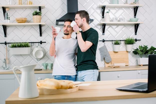 Ludzie, homoseksualizm, rodzina tej samej płci, koncepcja związków homoseksualnych. mężczyzna para gejów przytulanie siebie i picie porannej kawy stojąc w kuchni w domu