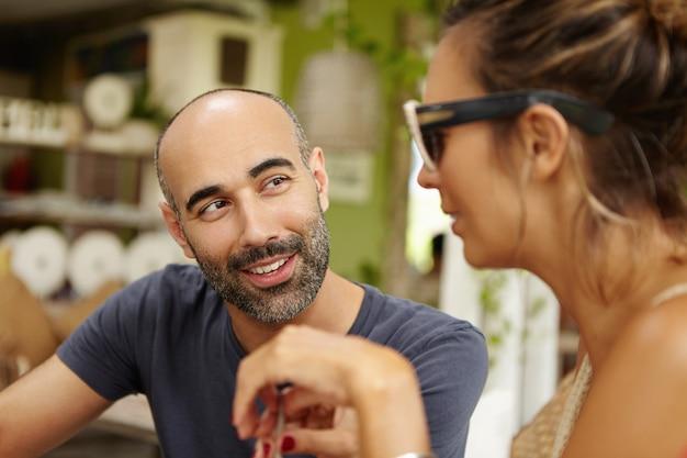 Ludzie i czas wolny. ożywiona rozmowa w kawiarni na chodniku z uroczą parą.
