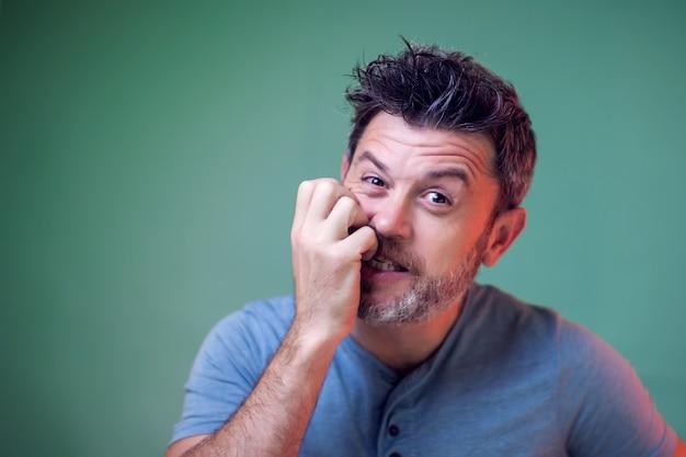 Ludzie i emocje - portret nerwowego mężczyzny zagryzł paznokcie