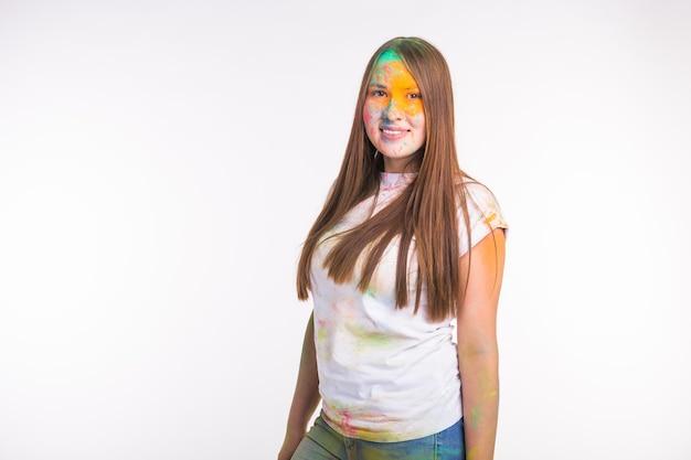 Ludzie i indyjskie wakacje koncepcja - brunetka kobieta pokryta farbą holi na białej ścianie z miejsca na kopię.