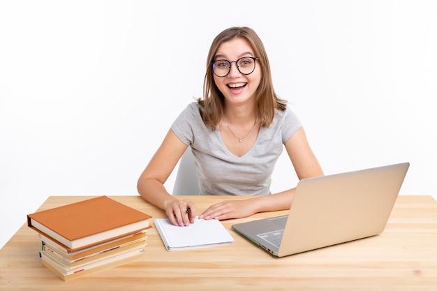 Ludzie i koncepcja edukacji - szczęśliwy studentka siedzi przy drewnianym stole z laptopem