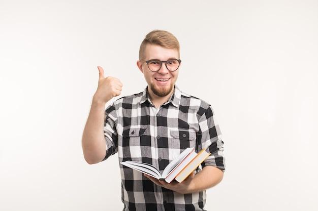 Ludzie i koncepcja edukacji - uśmiechnięty mężczyzna student trzymając książki i gestykuluje kciuki do góry na białym tle.