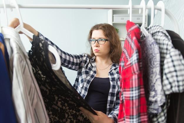 Ludzie i koncepcja sklepu mody - kobieta wybiera ubrania przed pełną szafą