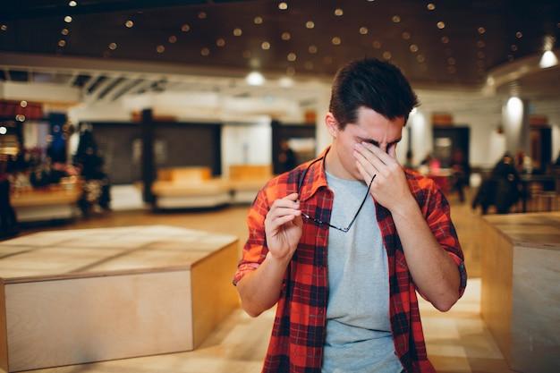 Ludzie i pracy pojęcie - zmęczony mężczyzna z eyeglasses w biurze