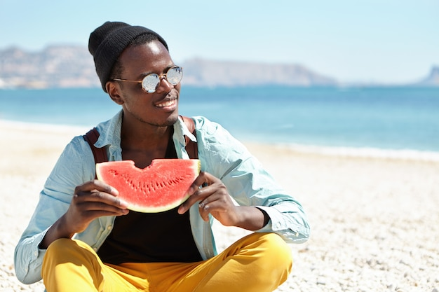 Ludzie i styl życia. podróż i turystyka. szczęśliwy, zrelaksowany młody afro american backpacker cieszący się słodkim soczystym arbuzem, siedzący ze skrzyżowanymi nogami na kamienistej plaży, trzymając dojrzałe owoce
