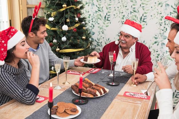 Ludzie jedzą cukierki przy świątecznym stole