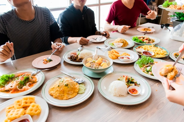 Ludzie jedzą jedzenie, a na stole jest dużo jedzenia.