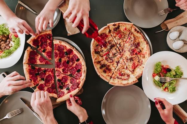 Ludzie jedzą pizzę w restauracji