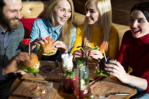 Ludzie jedzą razem obiad przy stoliku w kawiarni. szczęśliwi przyjaciele jedzą hamburgery i piją koktajle w restauracji
