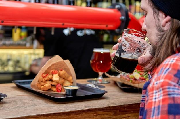 Ludzie jedzący fast foody spędzający razem czas w kawiarni, piwiarni. pyszne bryłki obiadowe w restauracji na drewnianym stole.