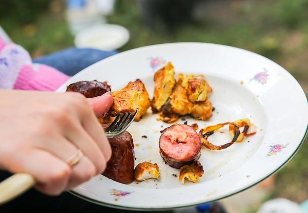 Ludzie jedzący grillowane warzywa i mięso. słodka papryka i pomidory. dobry w wiosce. styl rustykalny.