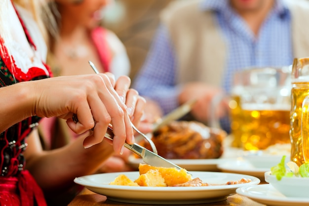 Ludzie jedzący pieczoną wieprzowinę w bawarskiej restauracji