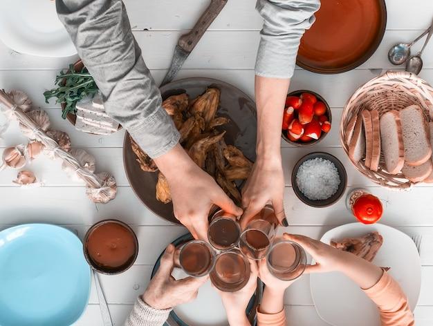 Ludzie jedzący posiłek i brzęczące szklanki