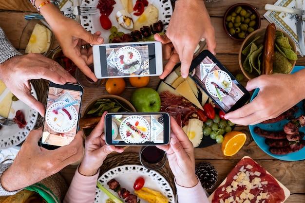 Ludzie jedzący razem robiący zdjęcie jedzenia smartfonem, aby udostępnić je w mediach społecznościowych