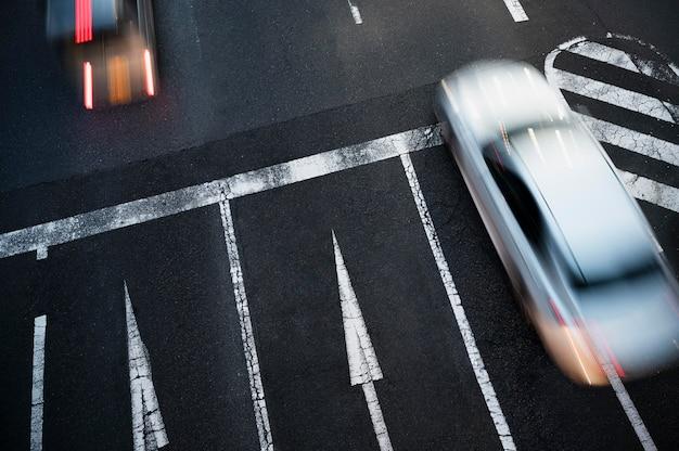 Ludzie jeżdżący samochodami po ulicy miasta
